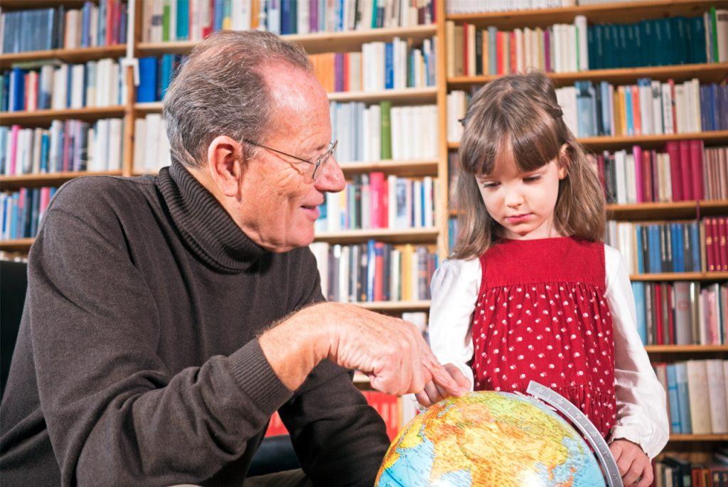 Дедушка с внучкой смотрят на глобус
