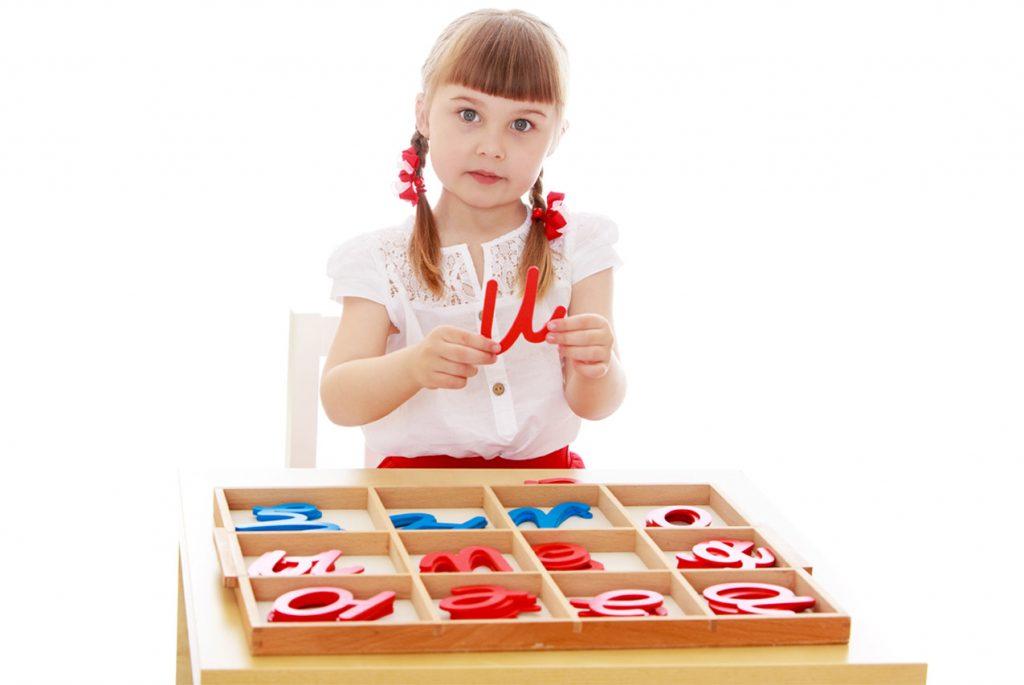 Девочка работает с подвижным алфавитом