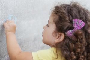 Девочка рисует на стене