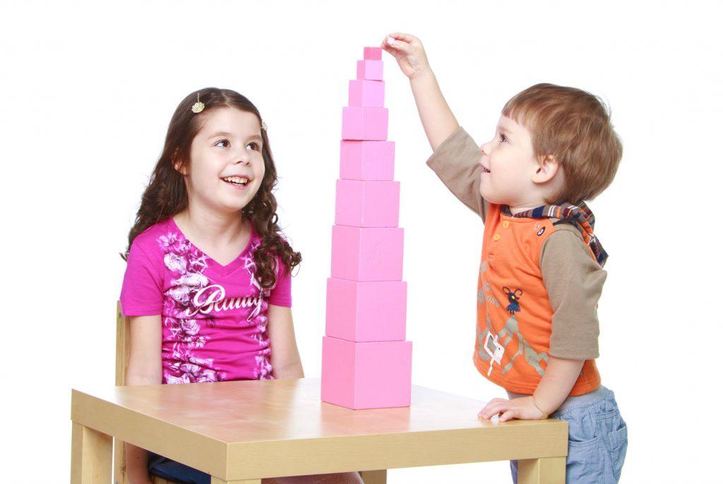 Девочка смотрит, как мальчик строит розовую башню
