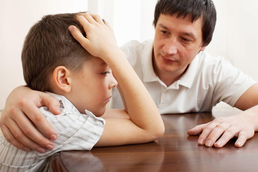 Отец пытается утешить грустного мальчика