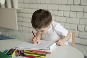 Мальчик рисует фломастерами