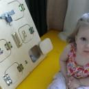 Маленькая девочка сидит рядом с бизибордом