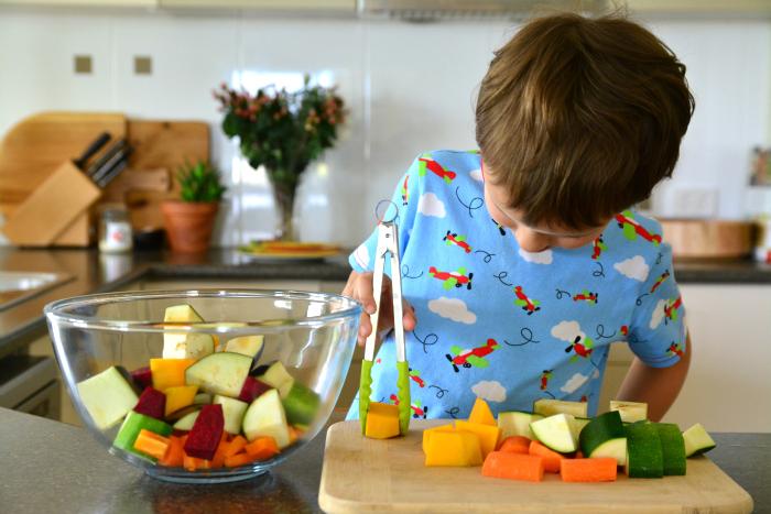 Мальчик с щипцами на кухне