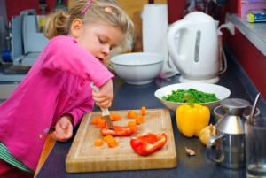 Девочка режет сладкие перцы на кухне