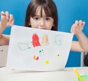 Маленька девочка показывает рисунок, который она нарисовала