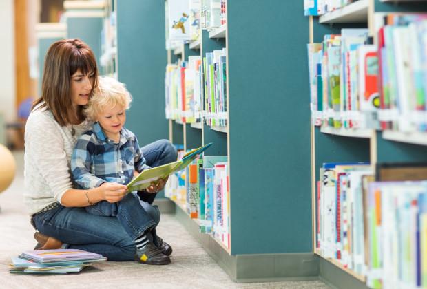 Мама читает маленькому сыну в библиотеке