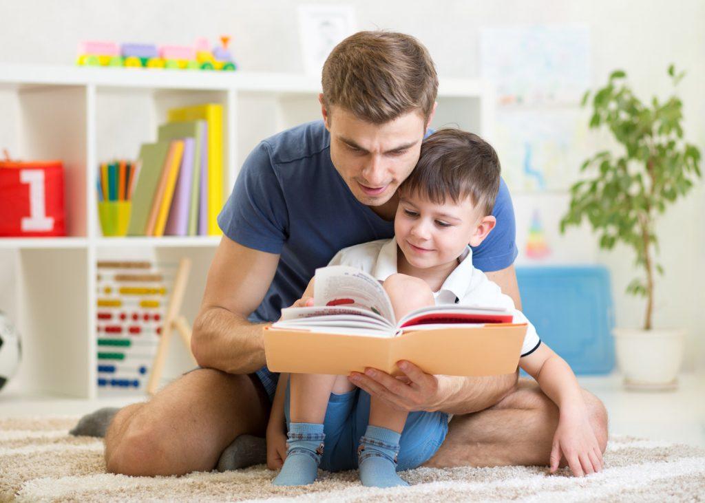 Папа читает маленькому сыну книгу в комнате
