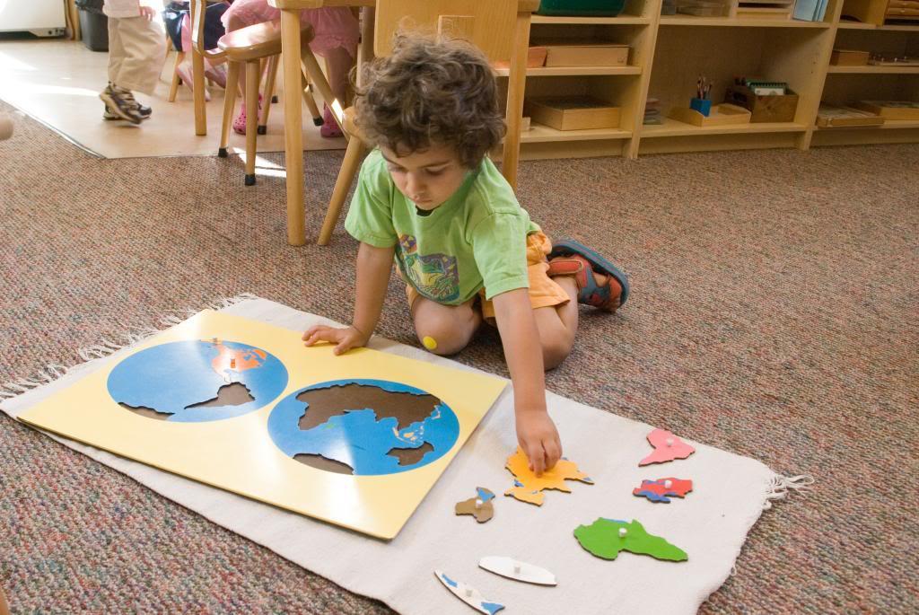 Мальчик работает с картами, изучая географию