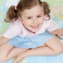 Маленькая девочка сидит на карте мира и довольно улыбается