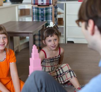 Две девочки внимательно смотрят на Монтессори-педагога, который показывает презентацию в классе