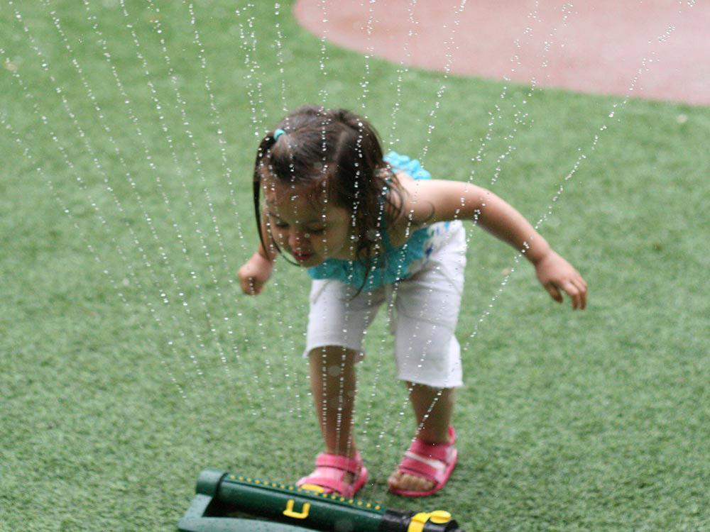 Девочка играет с брызгами воды