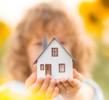 Маленький ребенок держит в руках игрушечный домик