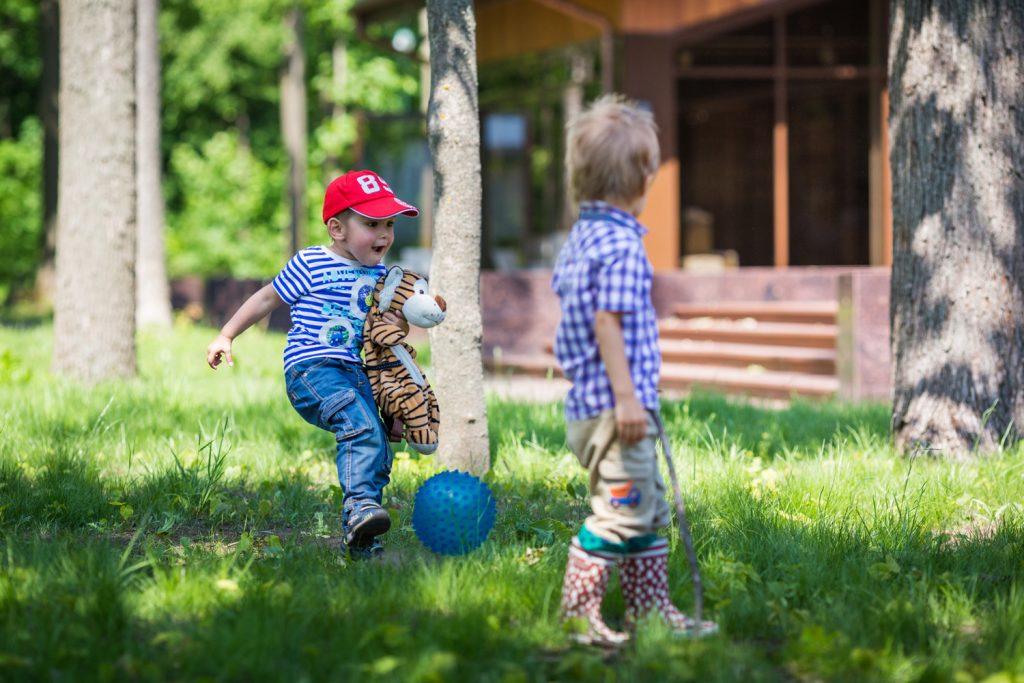 Маленький мальчик пинает мяч