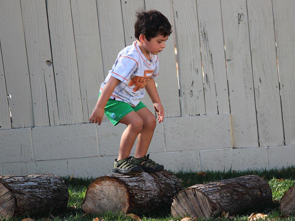 Мальчик прыгает по пням