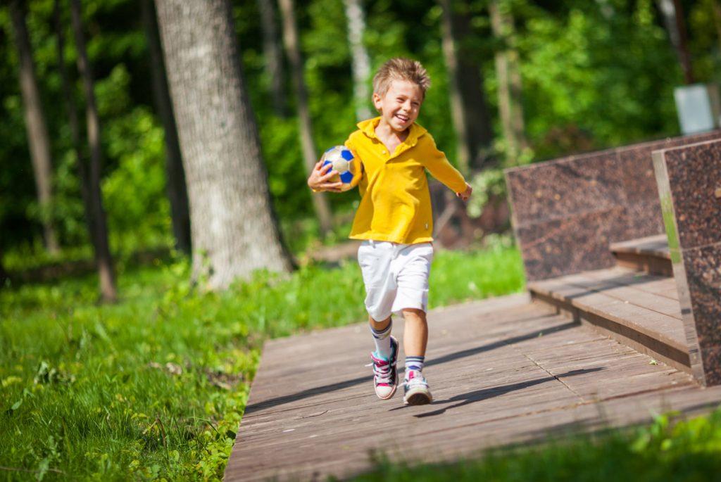 Счастливый мальчик бежит с мячом по дорожке