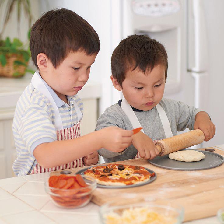 Два брата готовят на кухне пиццу