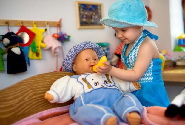 Маленькая девочка кормит куклу игрушечным бананом