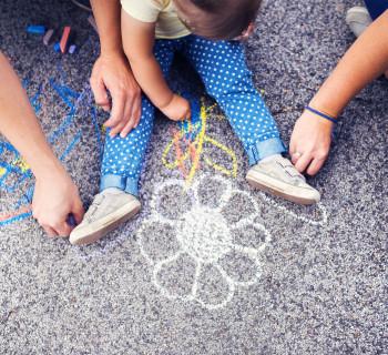 Мама, папа и ребенок рисуют на асфальте мелками