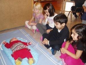 Дети наблюдают за дочкой, лежащей на топпончино