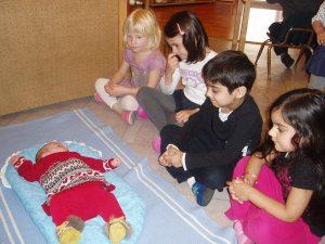 Дети наблюдают за дочкой, лежащей на топпончино.