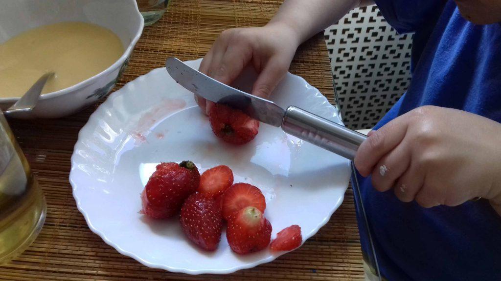 Ребёнок режет клубнику