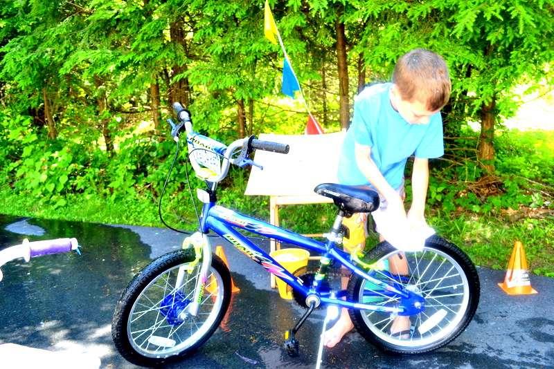 Ребенок моет велосипед