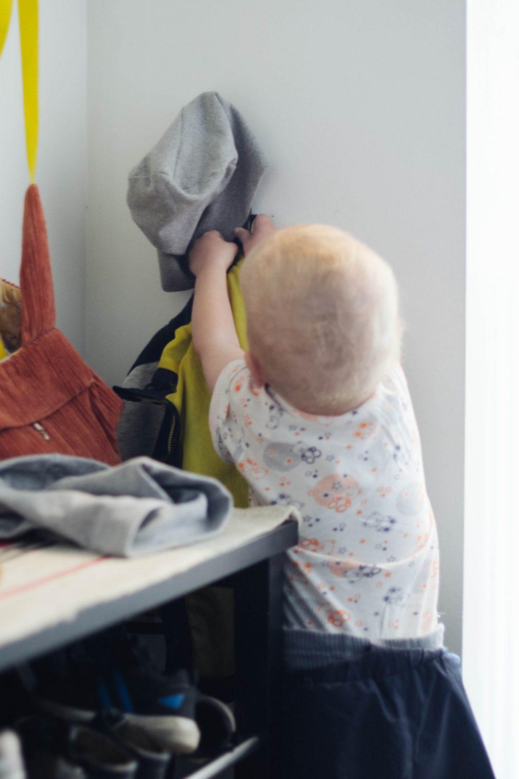 Ребёнок вешает куртку на крючок