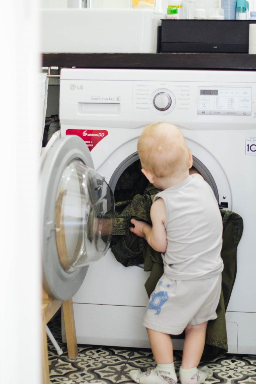 Ребёнок достаёт остатки одежды из стиральной машинки