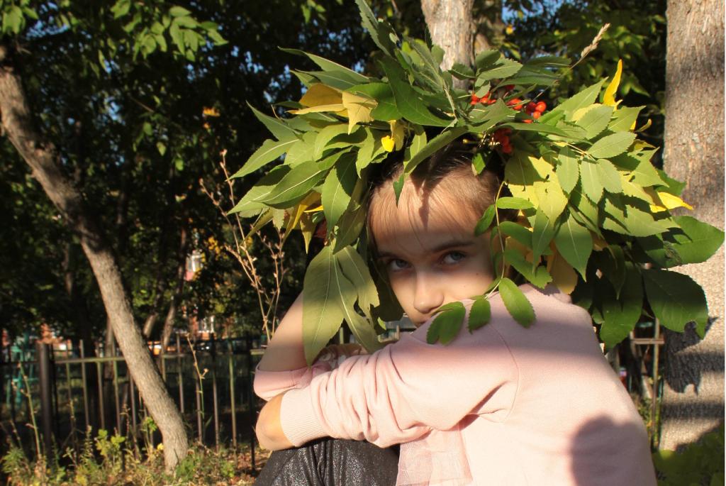 Ребёнок в осеннем венке из листьев