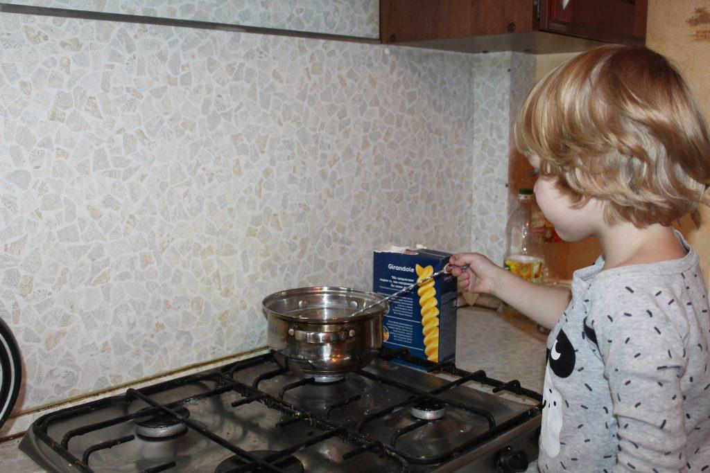 Ребёнок варит макароны