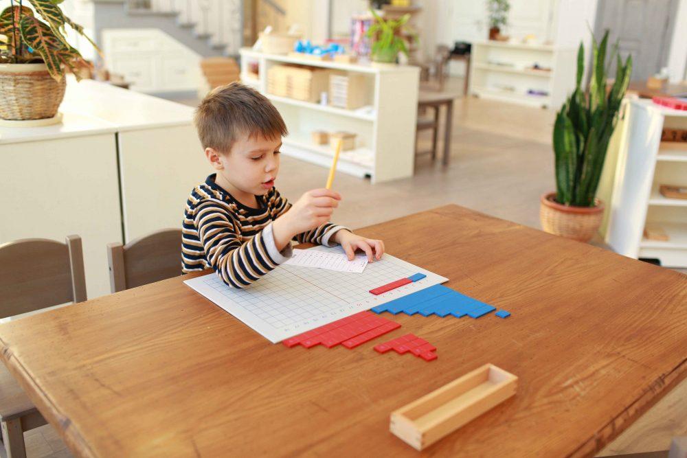Мальчик занимается математикой с Монтессори-материалами