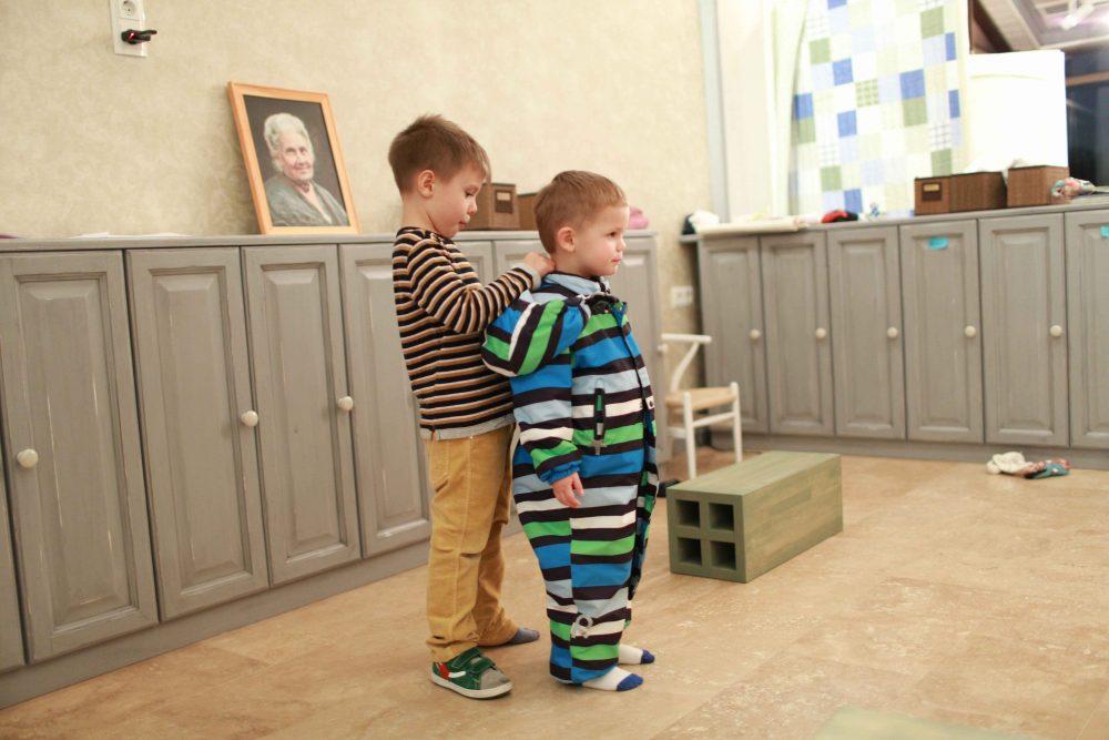 Ребёнок помогает одеться малышу