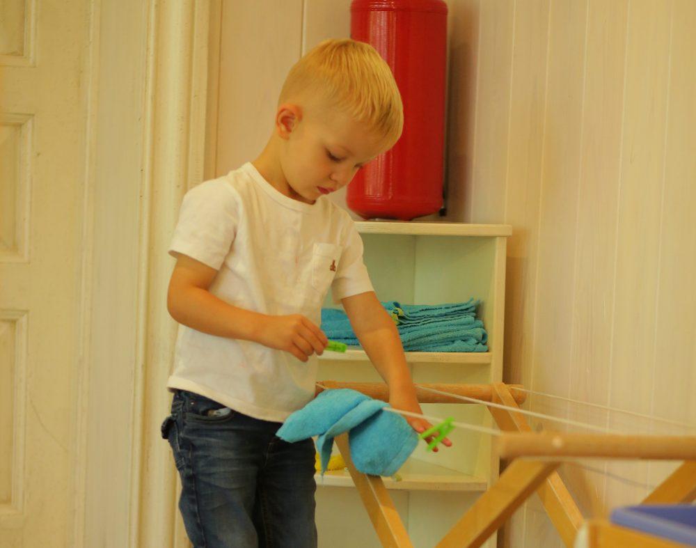 Ребёнок развешивает бельё