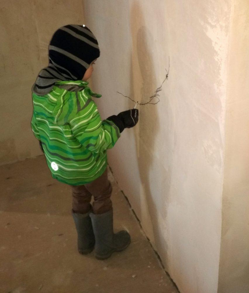 Ребёнок раскрашивает стену