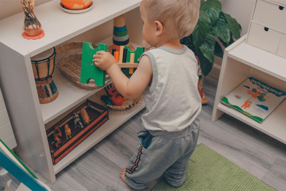 Ребёнок убирает игрушки на место