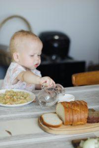 Ребёнок наливает воду из кувшина в стакан
