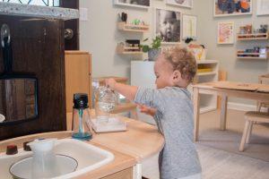 Ребёнок наливает воду в кувшин