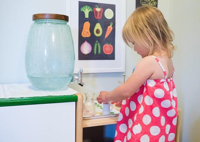 девочка наливает воду из диспенсера