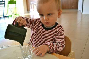 ребёнок наливает сам воду из кувшина в стаканчик