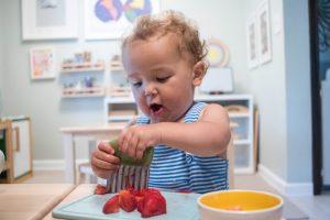 малыш нарезает ягоду