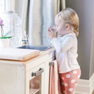 ребёнок набрал воды из диспенсера и пьёт
