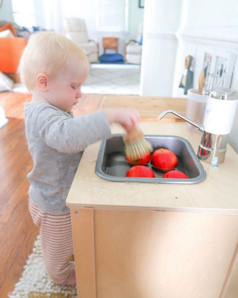 ребёнок моет яблоки