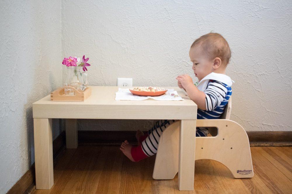 ребёнок ест за своим столиком