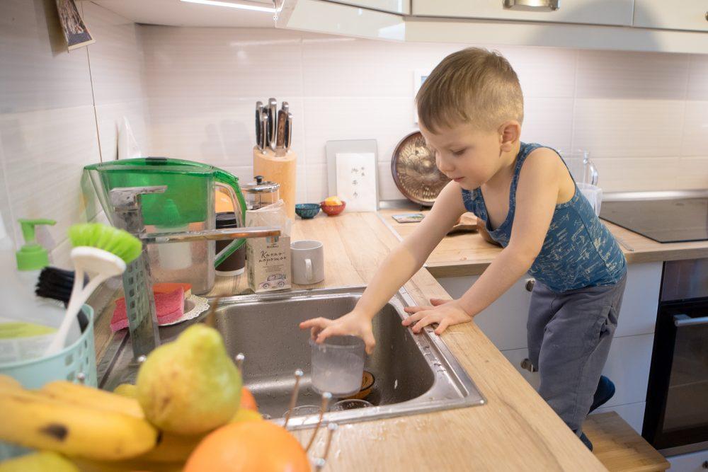 ребёнок убирает грязную посуду в раковину
