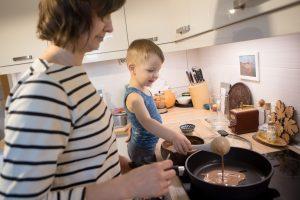 Ребёнок наливает тесто на скоровороду