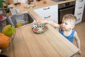 Ребёнок складывает посуду на стол