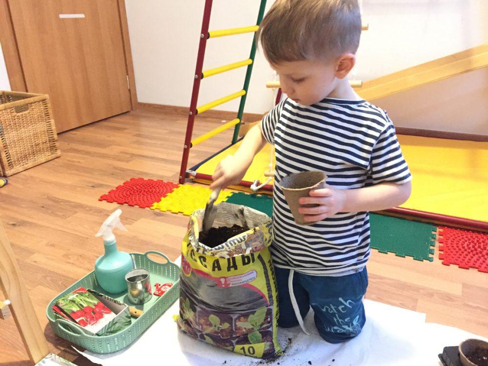 Ребёнок набирает землю в горшочки