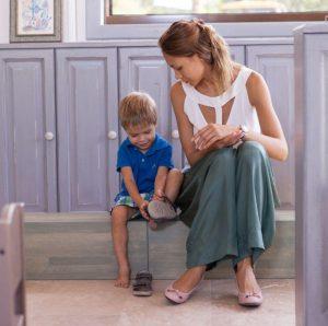 Мама смотрит как ребёнок обувается сам