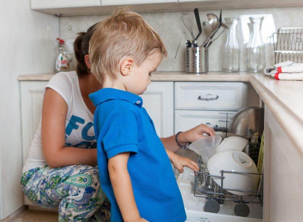 Мальчик загружает посуду в посудомойку